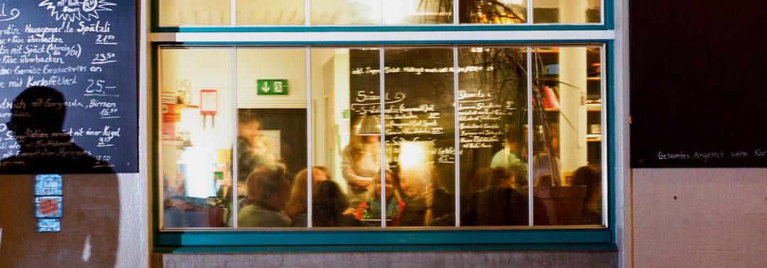 Abendlicher Blick durch das Fenster ins Café Zähringer, Zürich